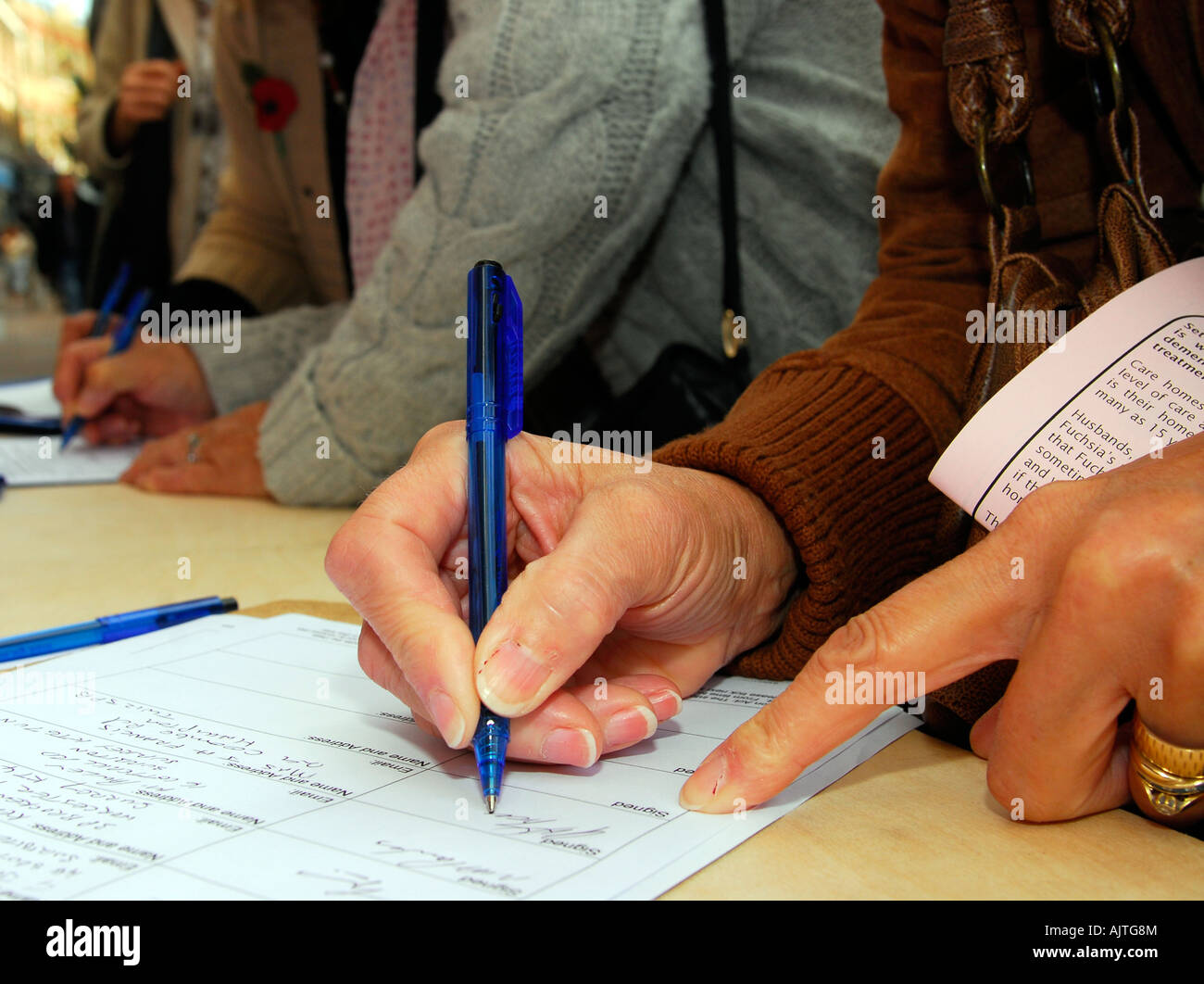 Members of the public signing a petition against cuts in mental health services, Kingston, Surrey, UK. - Stock Image