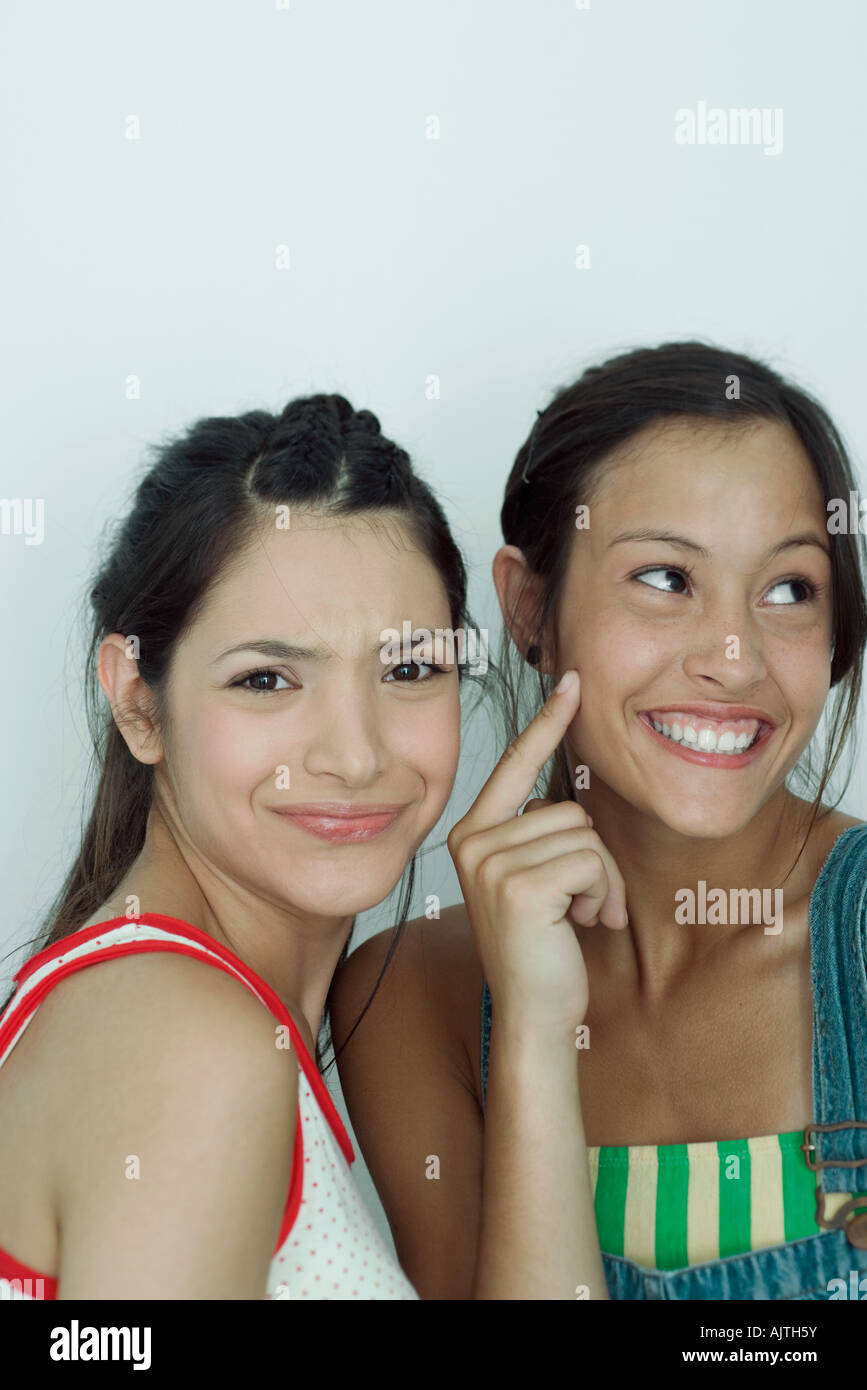 Two young female friends, one furrowing brow at camera, the other pointing to cheek, looking away, portrait - Stock Image