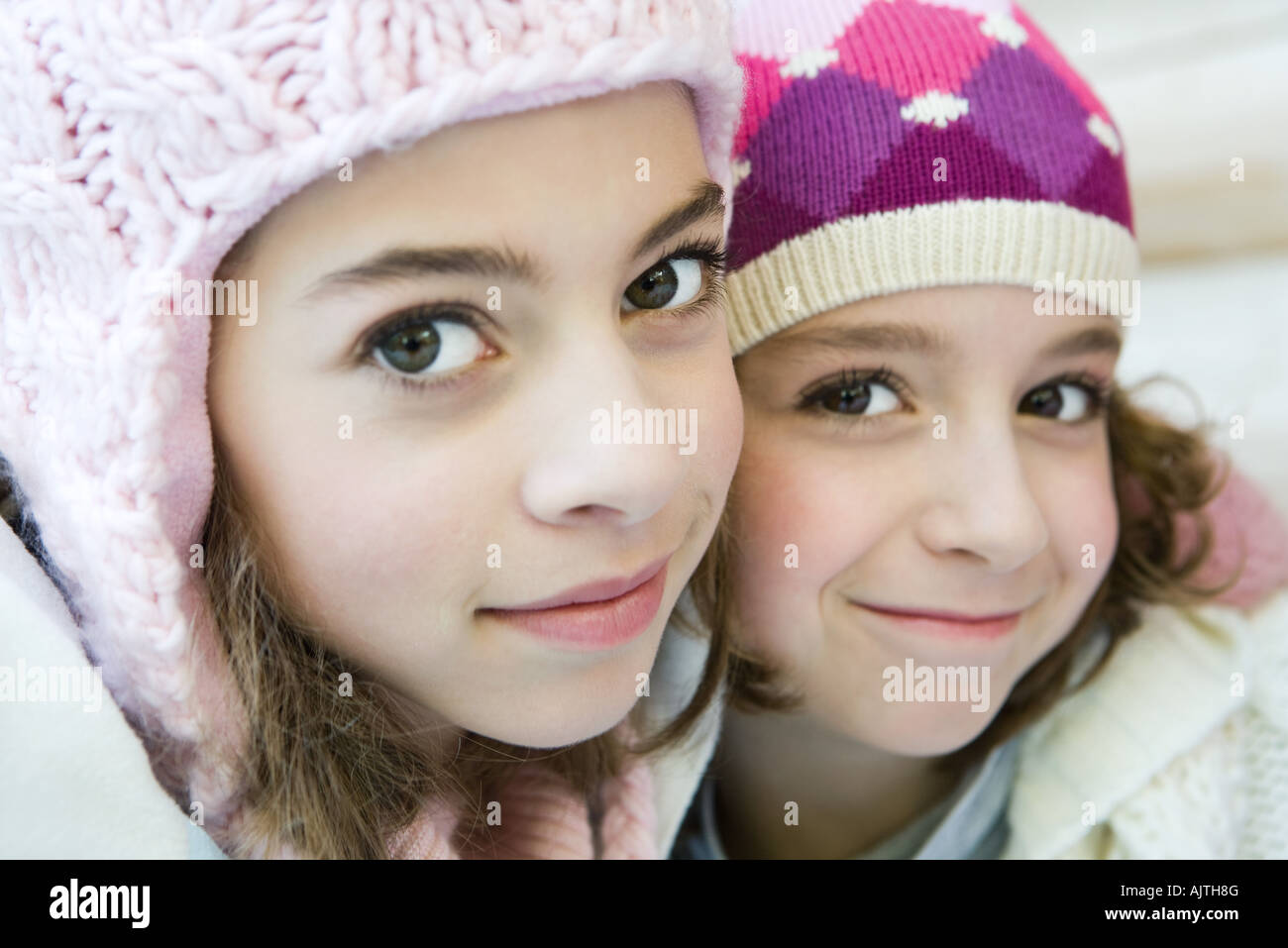 Two young sisters smiling at camera, both wearing knit hats, cheek to cheek, portrait - Stock Image