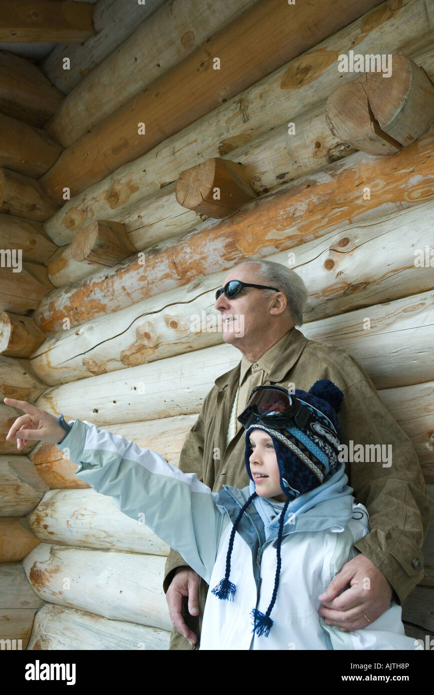 Grandfather and grandson standing together, boy pointing, both looking away - Stock Image