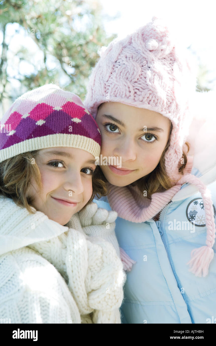 Two sisters smiling at camera, cheek to cheek, both wearing knit hats, portrait - Stock Image
