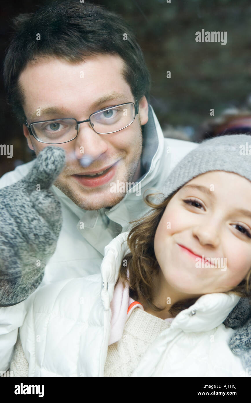 Young man looking over little sister's shoulder and pointing, both smiling at camera, portrait Stock Photo