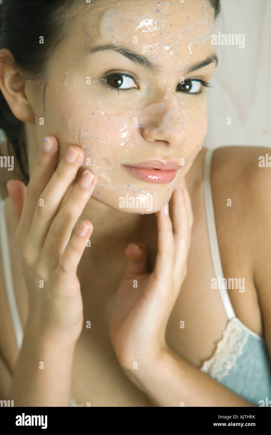 Young woman putting exfoliant mask on face, smiling at camera - Stock Image