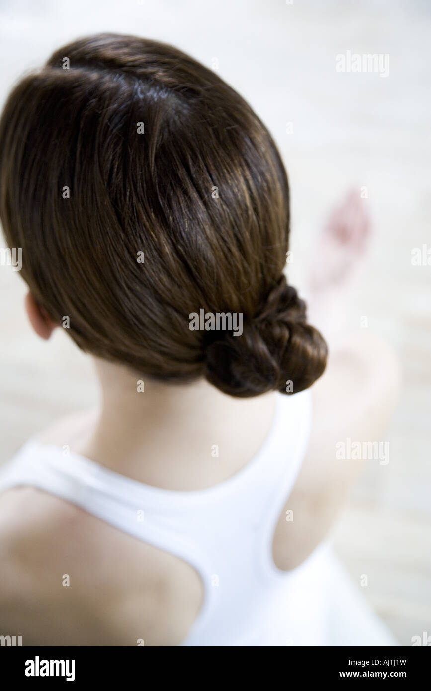 Brunette woman wearing hair in chignon, rear view - Stock Image