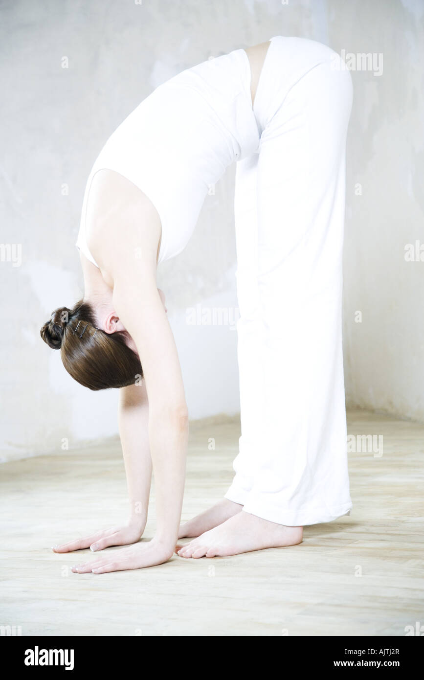 Woman bending over, touching toes, full length - Stock Image