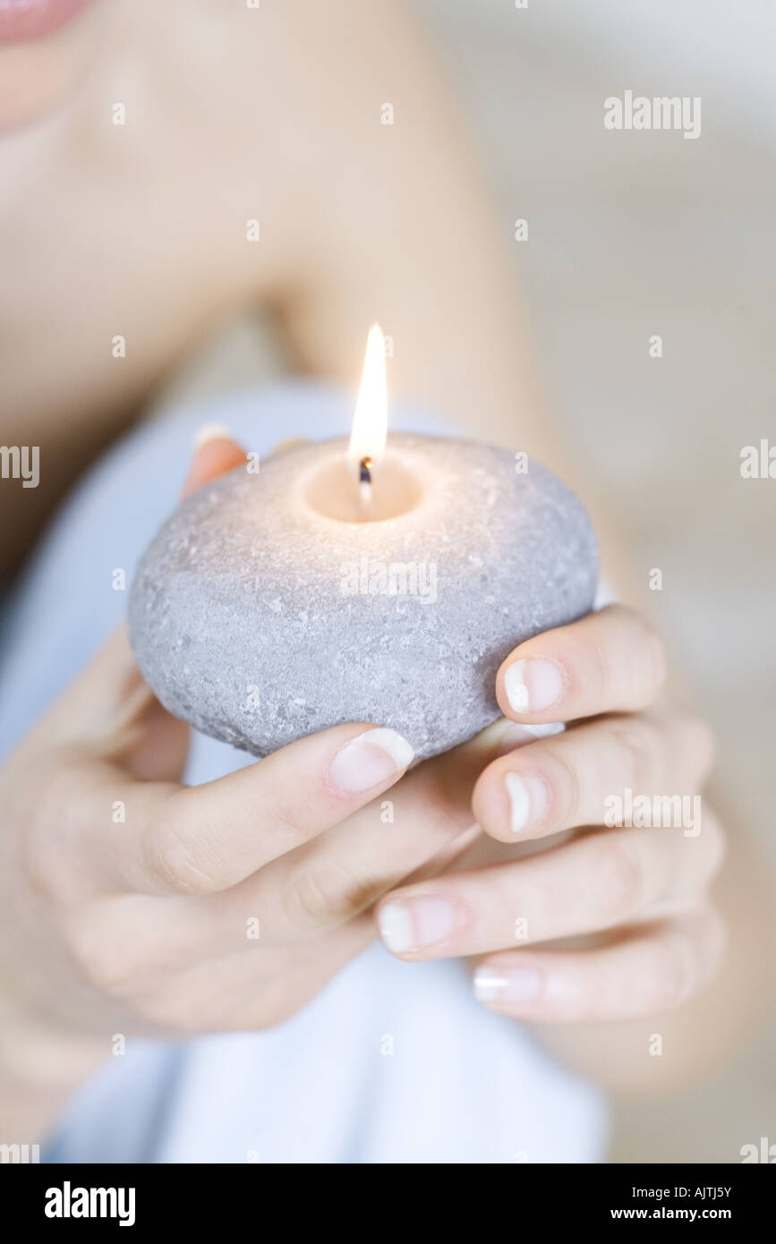 Woman holding burning candle, close-up view of hands - Stock Image