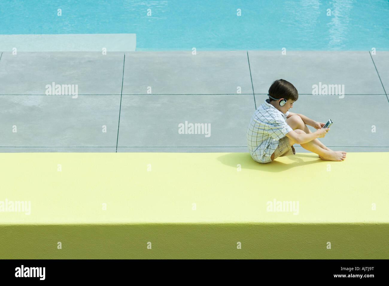 Boy sitting next to swimming pool, using handheld video device, wearing headphones Stock Photo