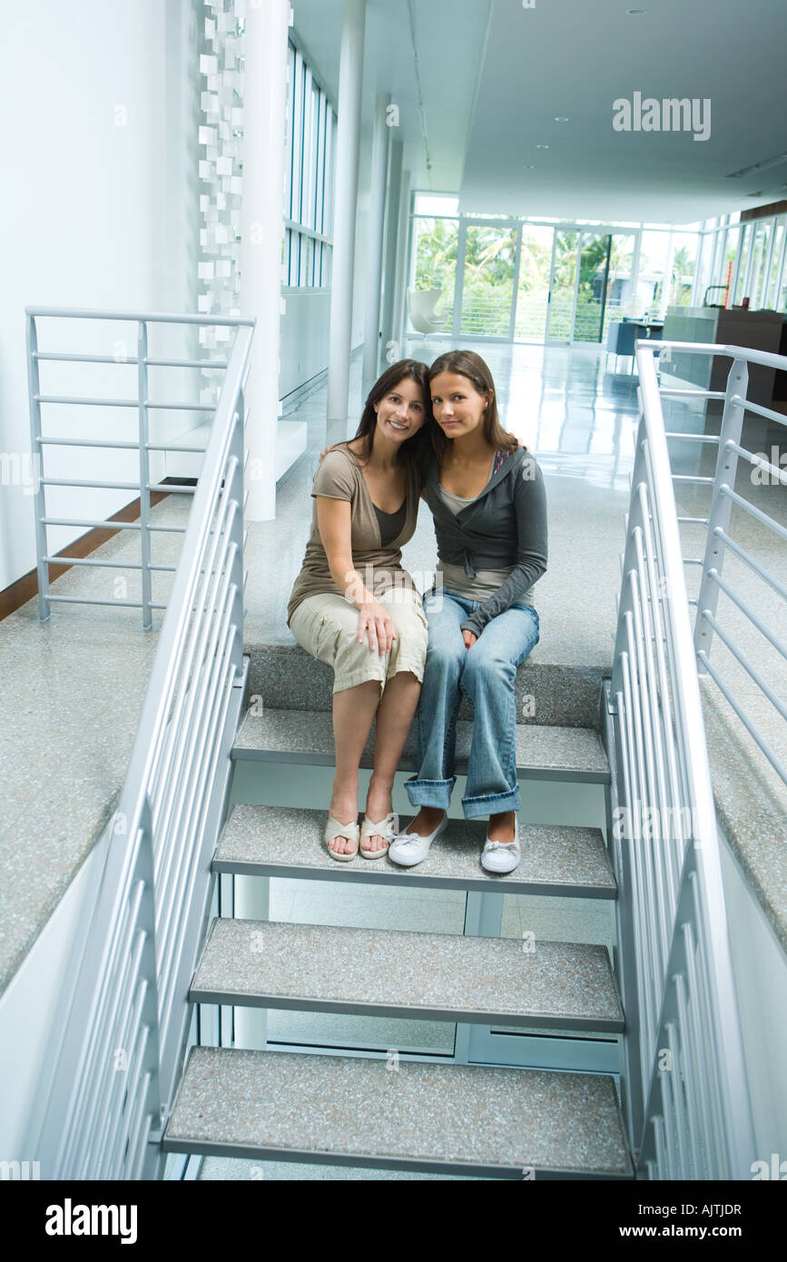 Mother and teenage girl together, sitting on steps, smiling at camera, full length Stock Photo