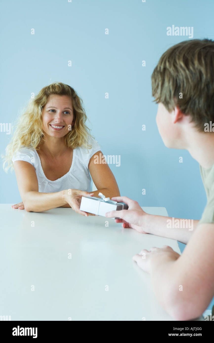 Teen boy handing mother present, both smiling at each other - Stock Image