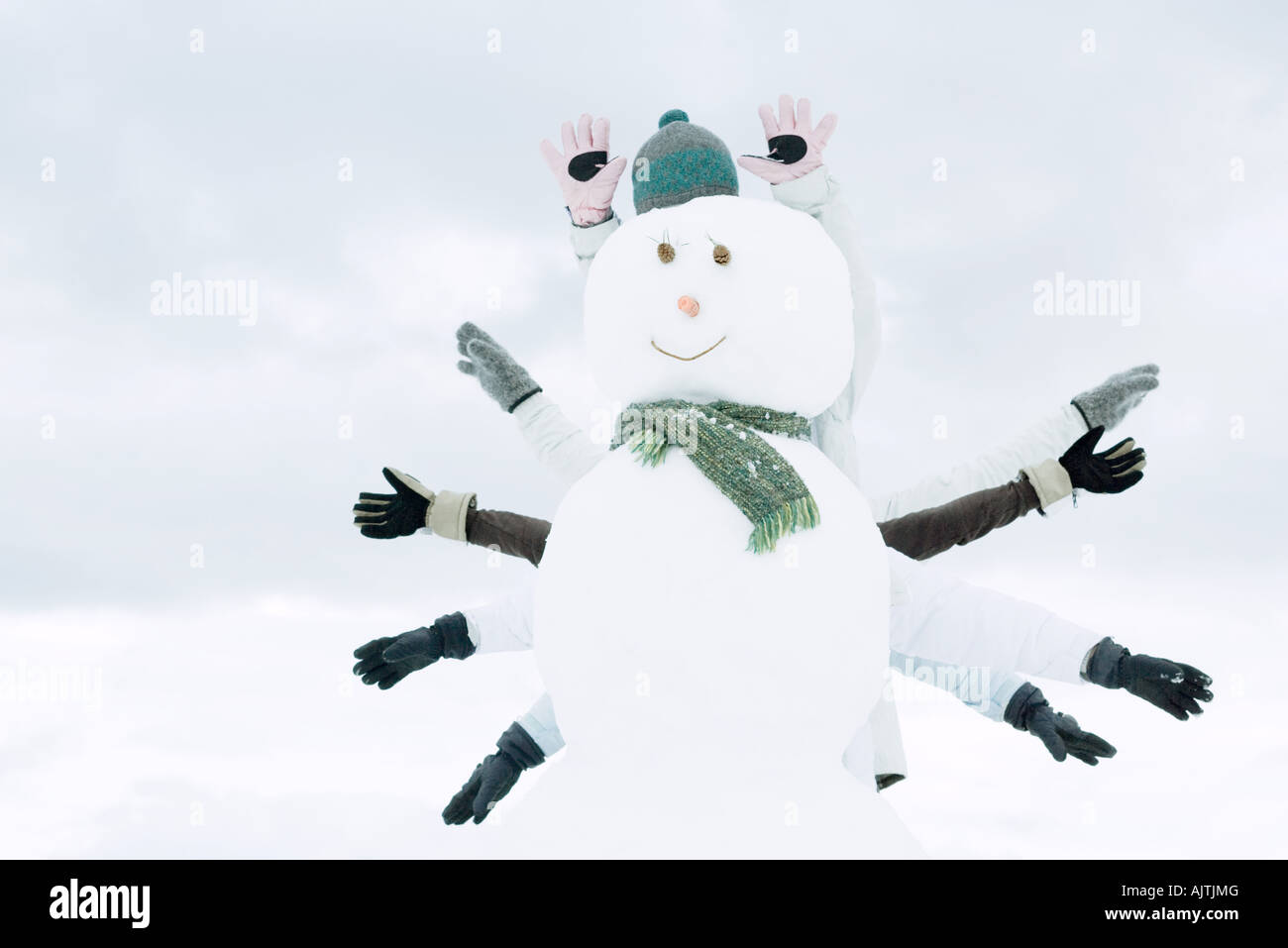 Snowman, several people's arms emerging from behind - Stock Image