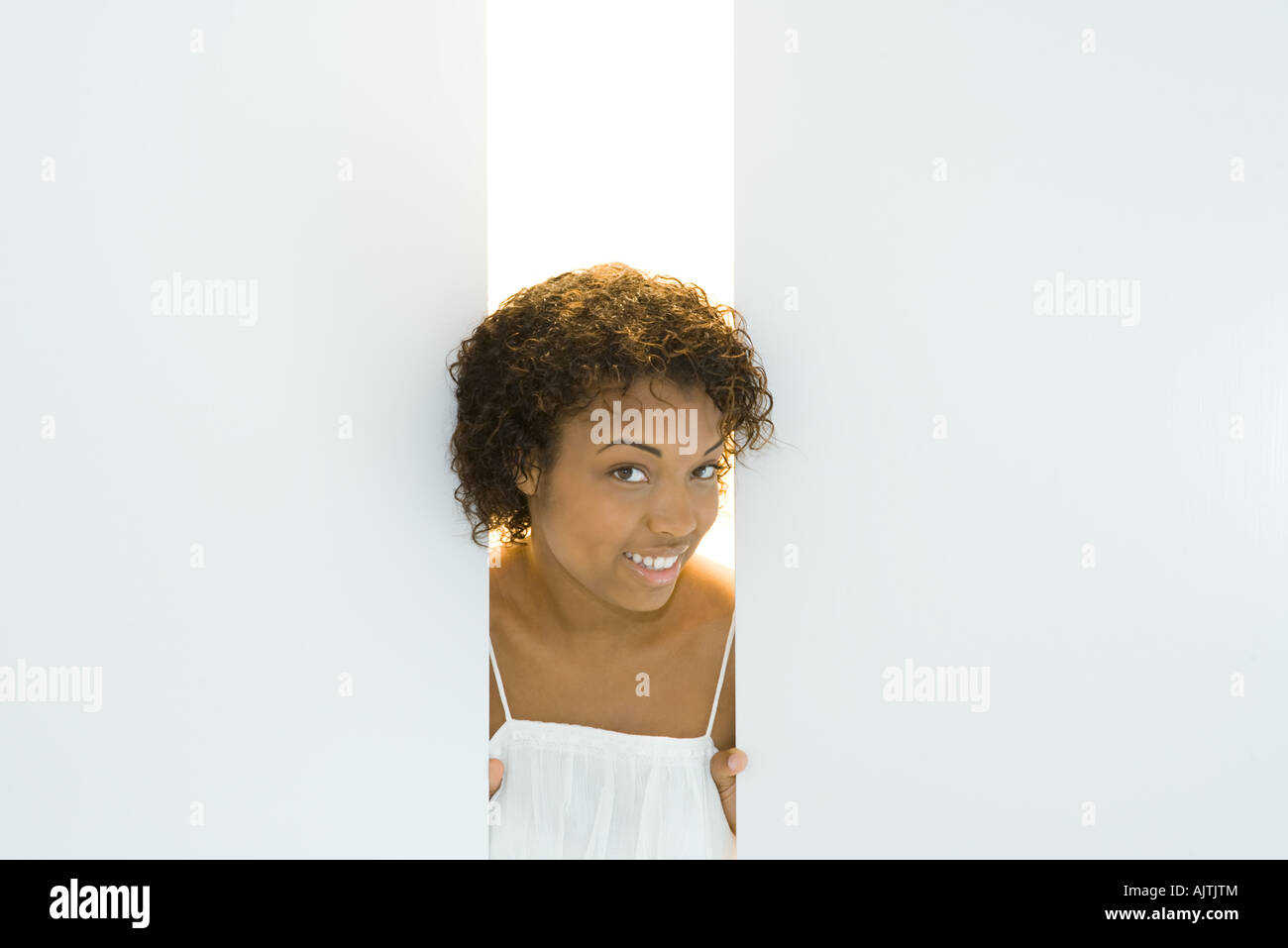 Young woman peeking through opening in walls, smiling at camera, portrait - Stock Image