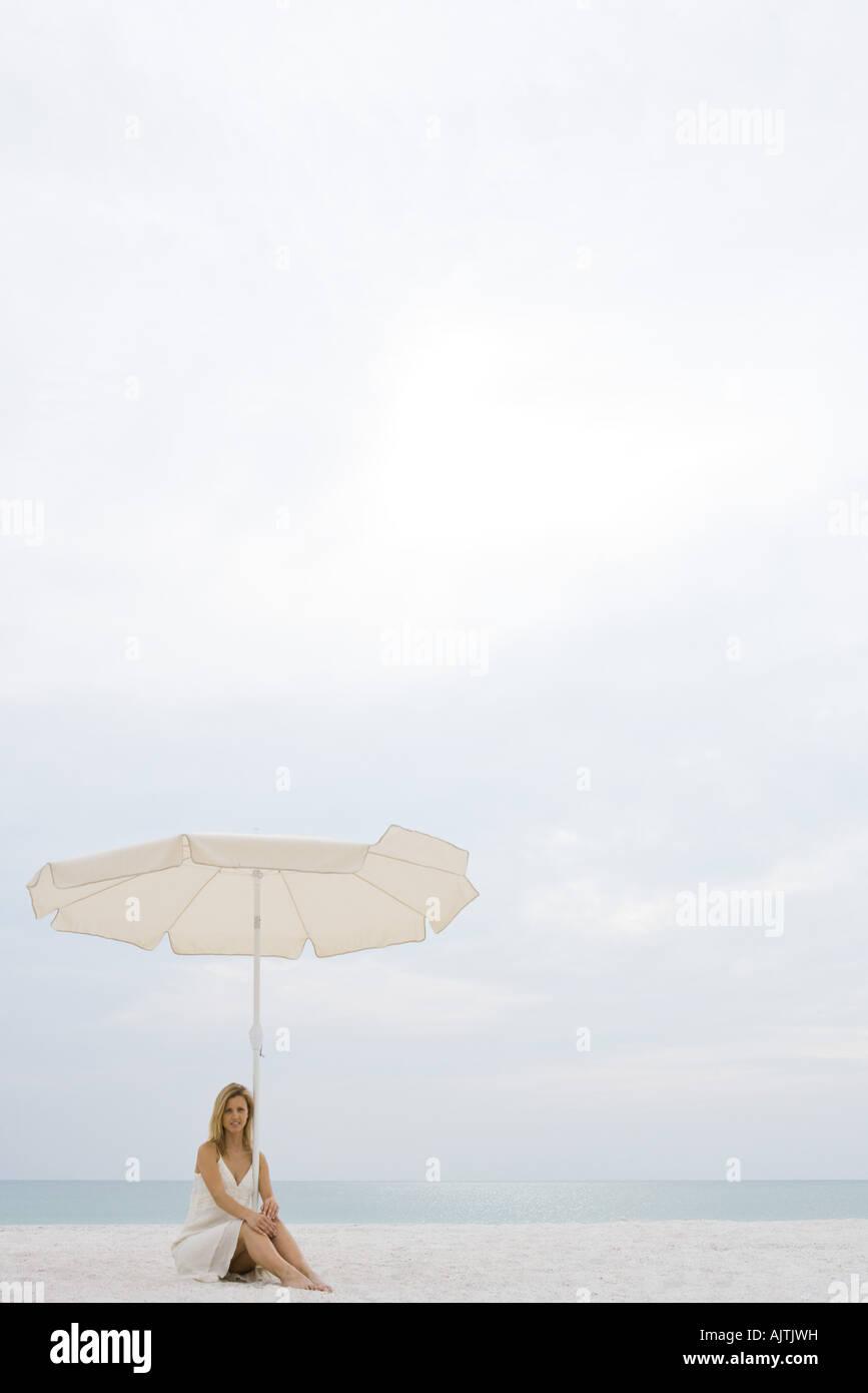 Woman wearing sundress, sitting under parasol on beach, full length - Stock Image