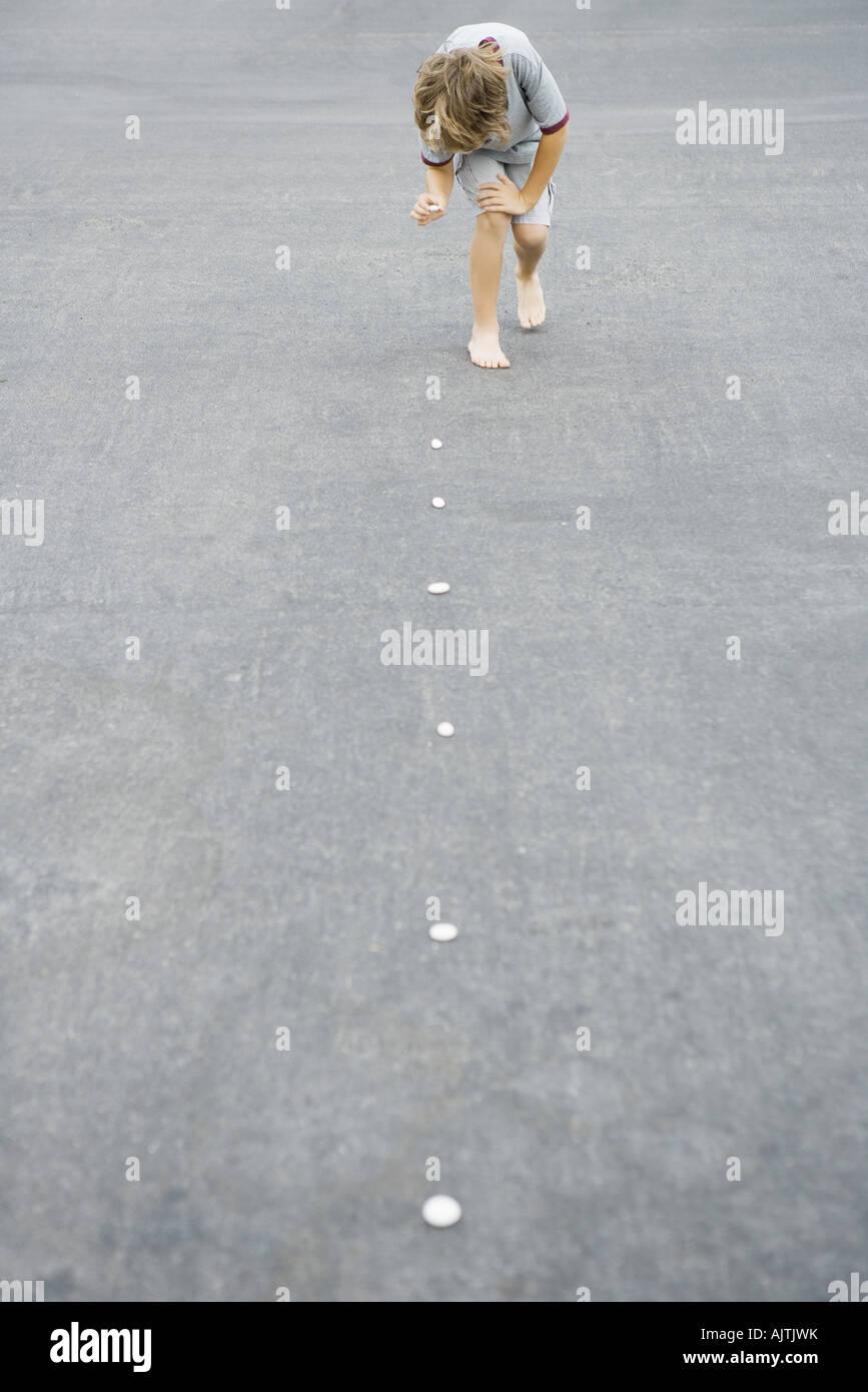 Boy placing trail of pebbles on asphalt - Stock Image