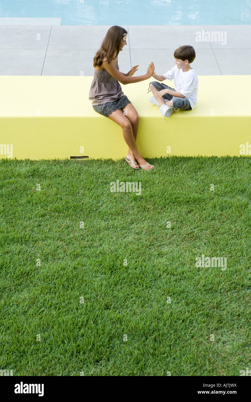 Mother And Boy Sitting Outdoors Playing Clapping Game High Angle