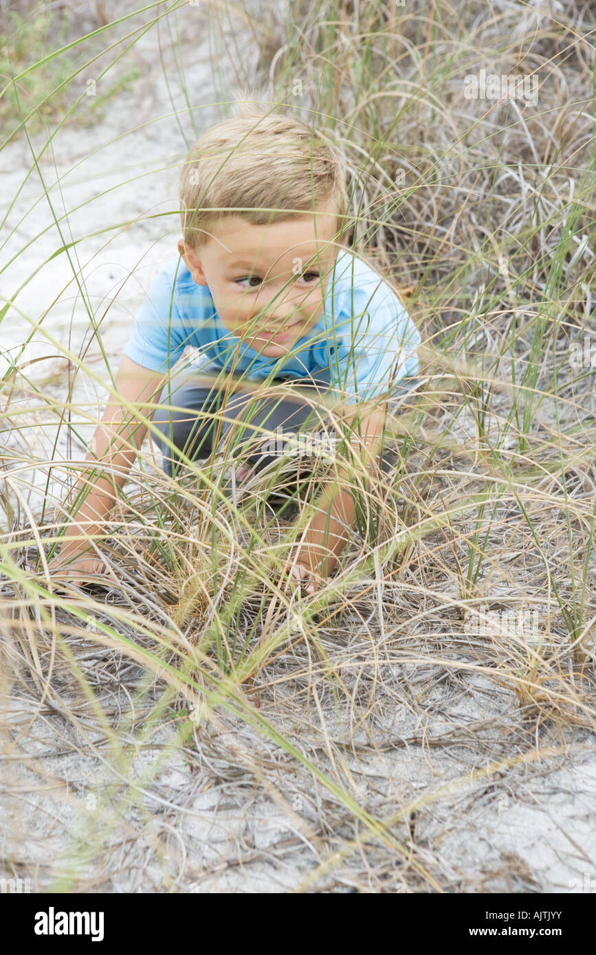 Boy crouching in dune grass, looking away mischievously, full length, high angle view - Stock Image