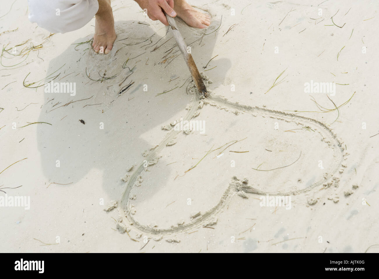 Man tracing heart in sand with stick, high angle view, cropped view - Stock Image