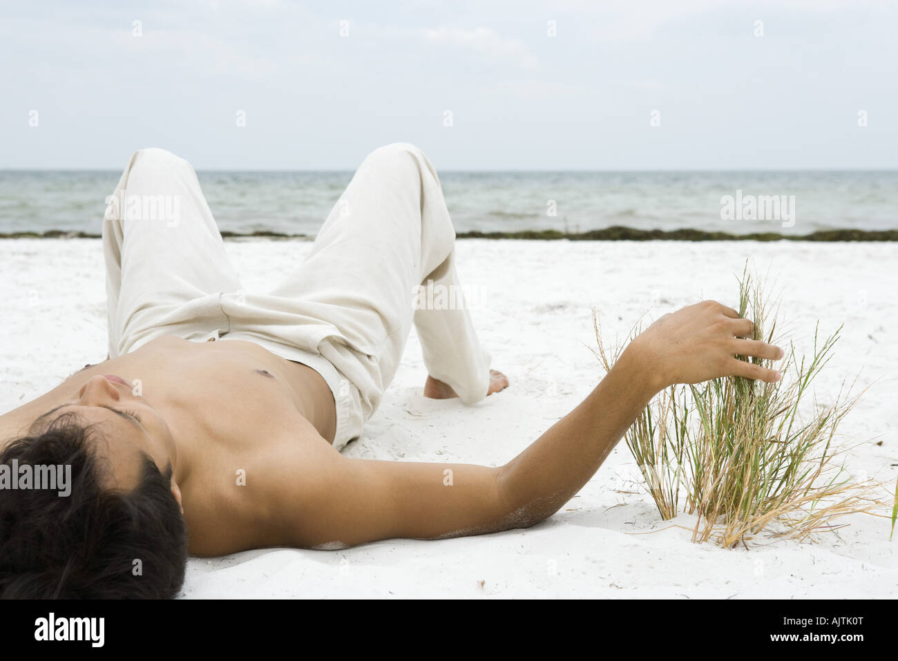 Young man lying on back on sand, touching dune grass, ocean in background - Stock Image