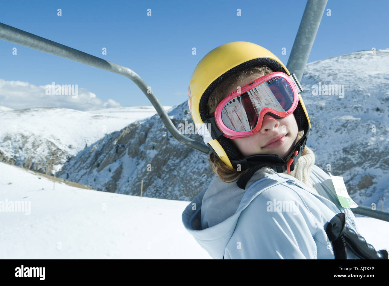 Teenage girl on ski lift, wearing goggles and helmet, looking at camera, portrait - Stock Image