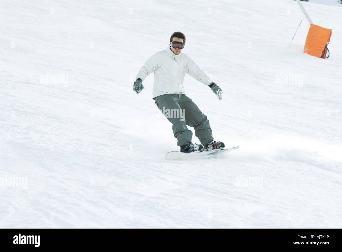 Young man snowboarding on ski slope, full length - Stock Image