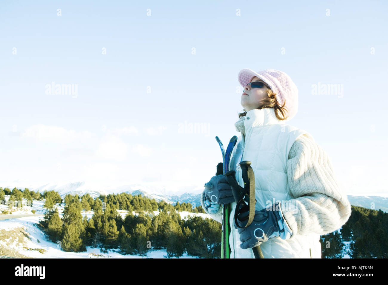 Young skier standing, looking up, side view - Stock Image