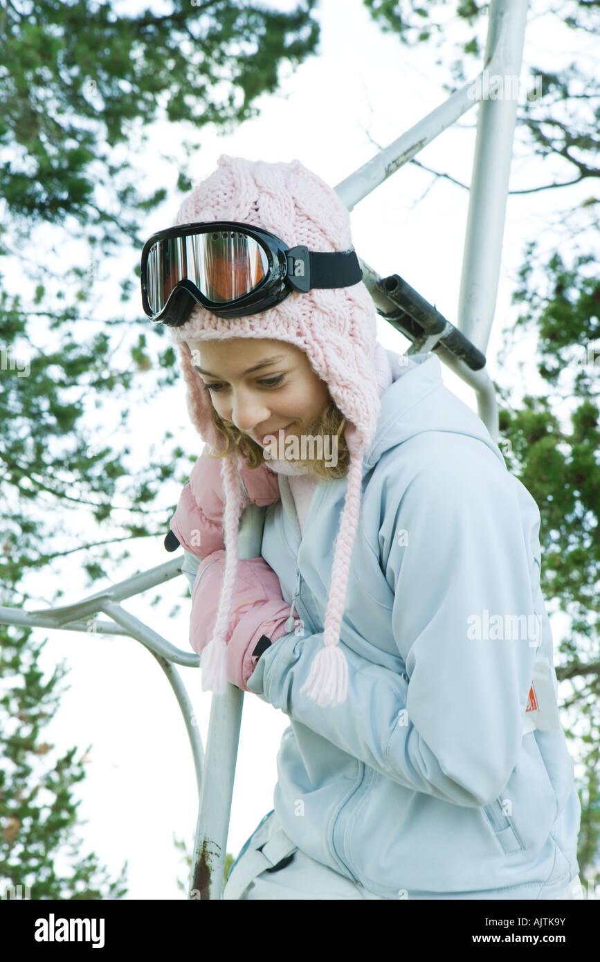 Teenage girl holding on to ski lift, looking over side - Stock Image