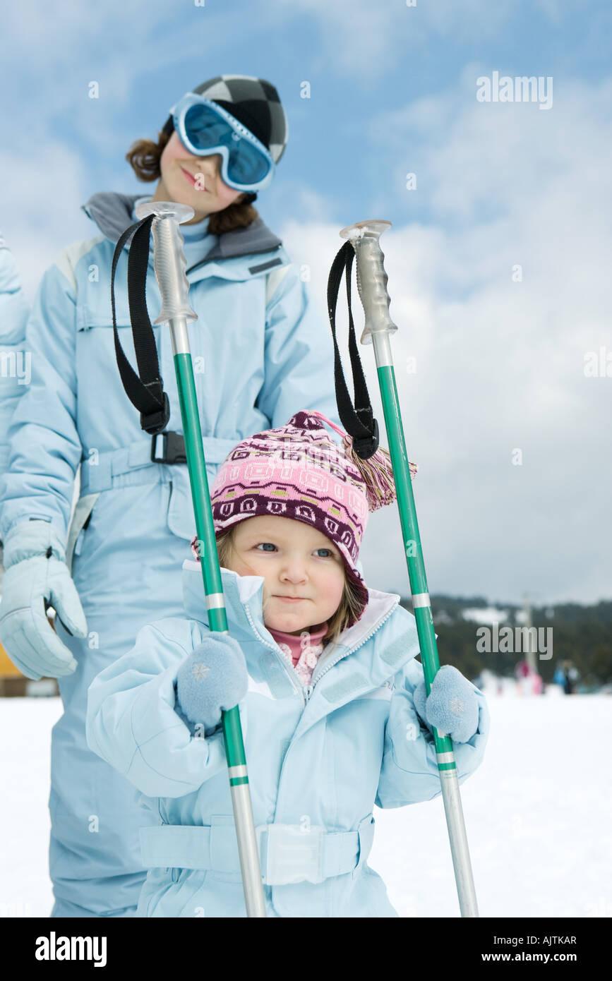 Toddler girl holding ski sticks, older sister standing behind, both wearing ski-suits - Stock Image