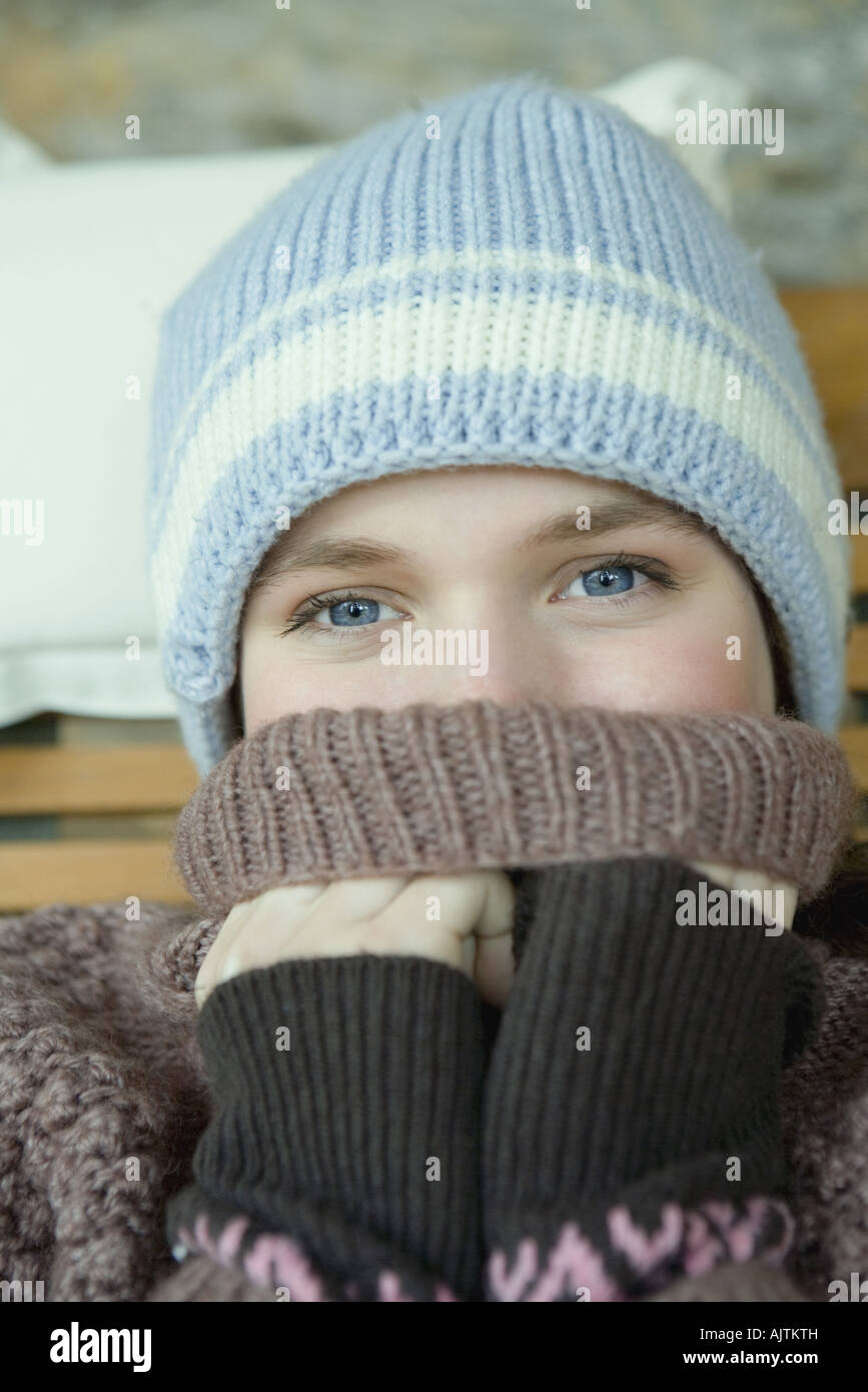 Teen girl covering mouth with turtle neck sweater, portrait - Stock Image