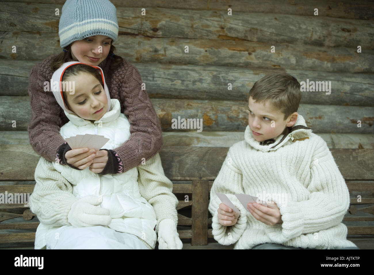 Young friends in winter clothes playing cards Stock Photo
