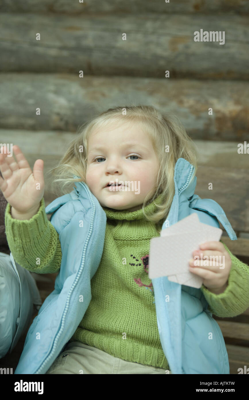 Toddler girl holding cards, motioning with hand - Stock Image