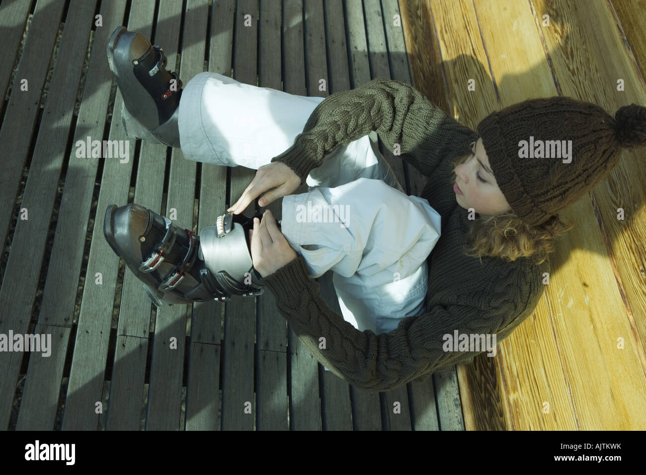 Teen girl putting on ski boots - Stock Image