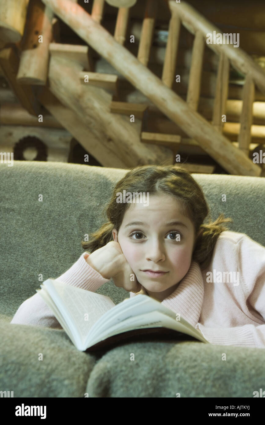 Preteen girl lying on sofa with book, looking at camera - Stock Image