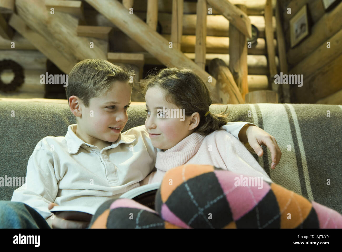 Preteen boy and girl with book, smiling at each other - Stock Image