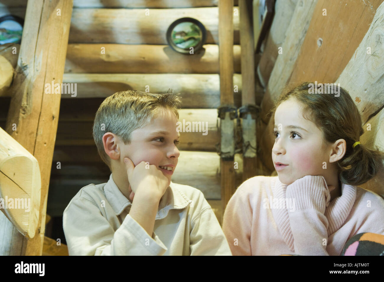 Preteen boy and girl sitting side by side, talking - Stock Image