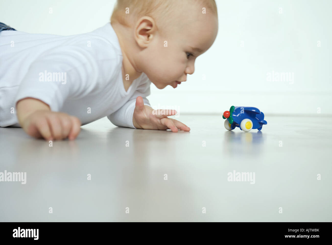 Baby lying on floor, looking at toy airplane - Stock Image