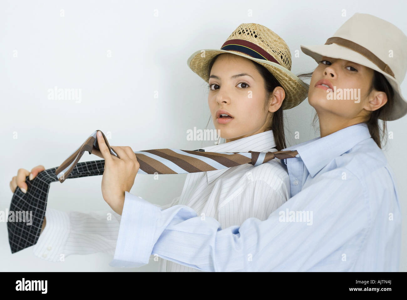 Two young female friends dressed in hats and ties, one behind the other, looking at camera - Stock Image