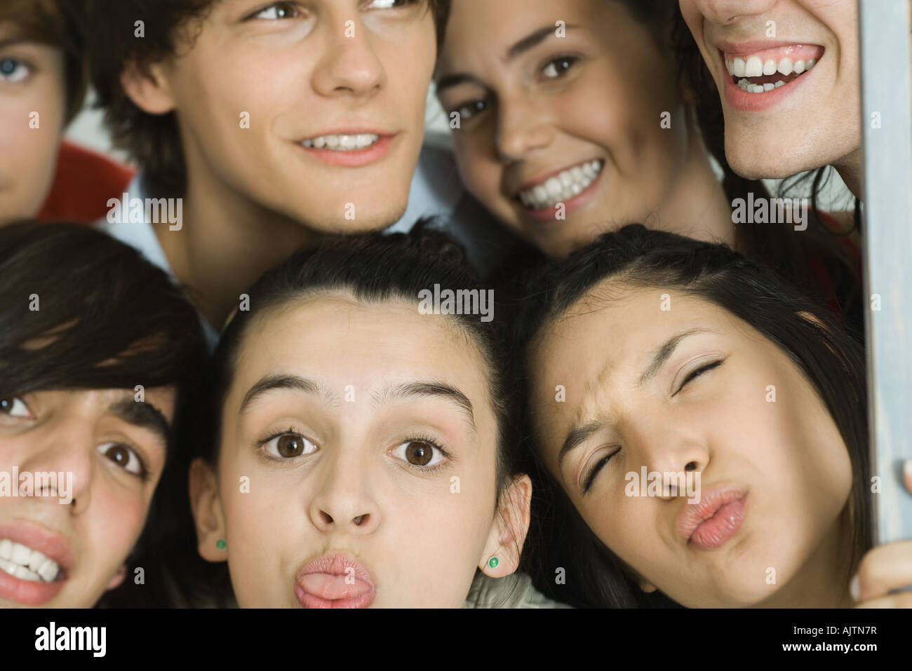 Group of young friends making faces at camera, cropped view - Stock Image
