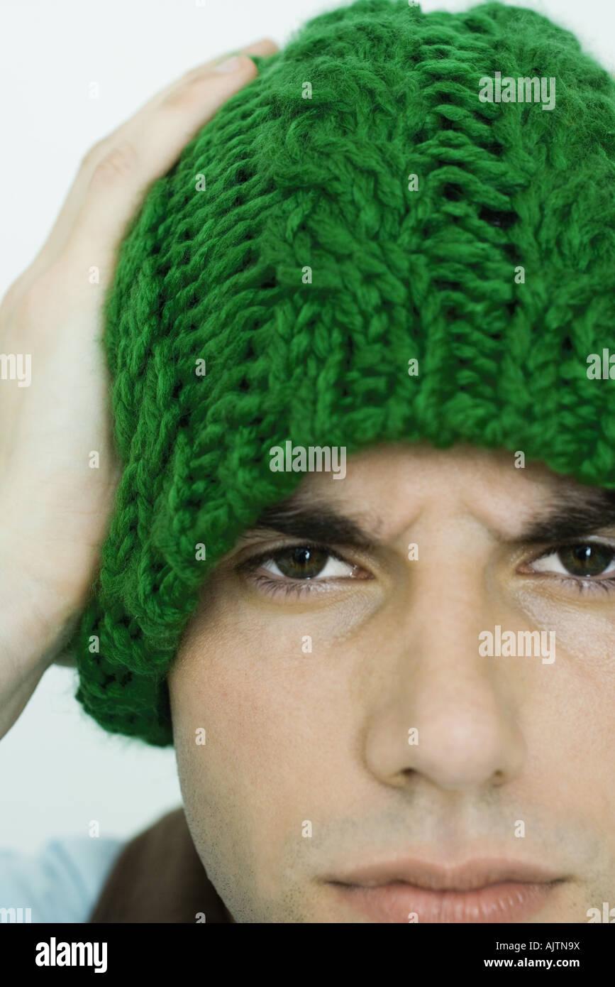 Young man wearing knit hat, looking at camera, furrowing brow - Stock Image