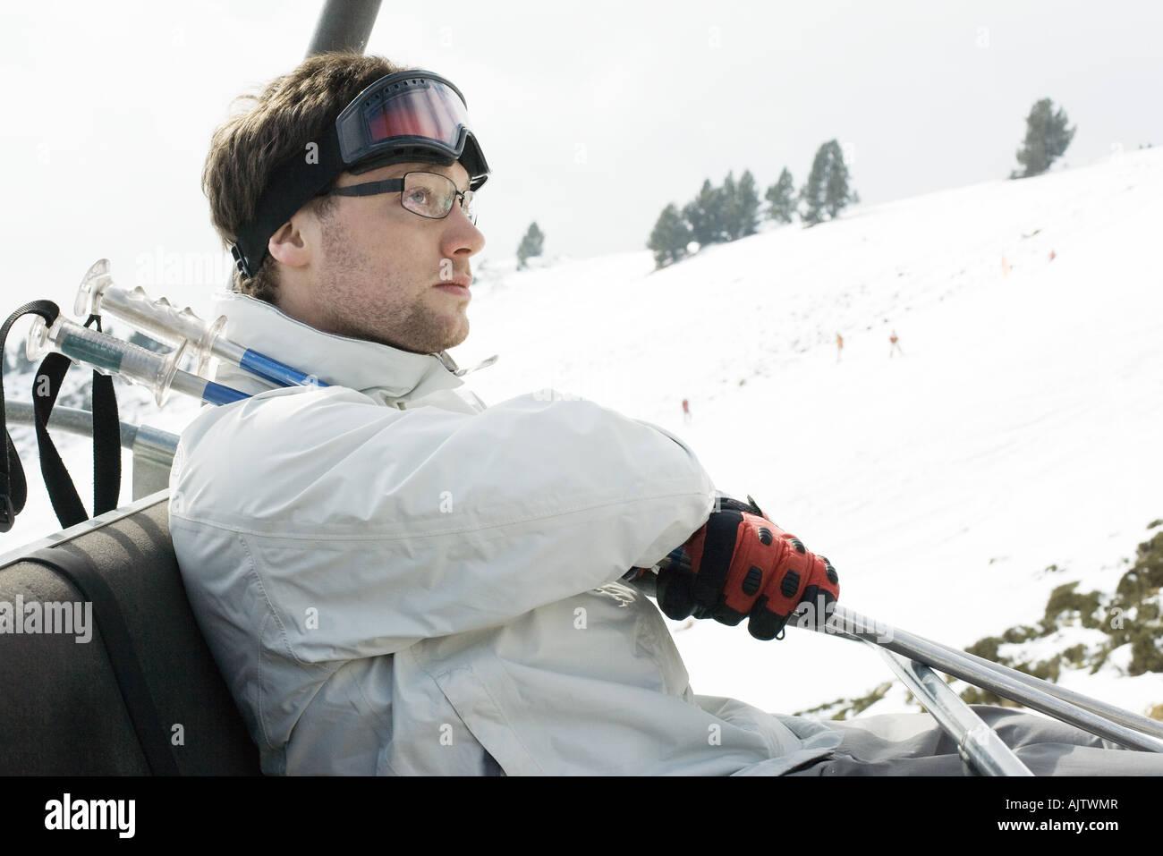 Young man taking ski lift Stock Photo