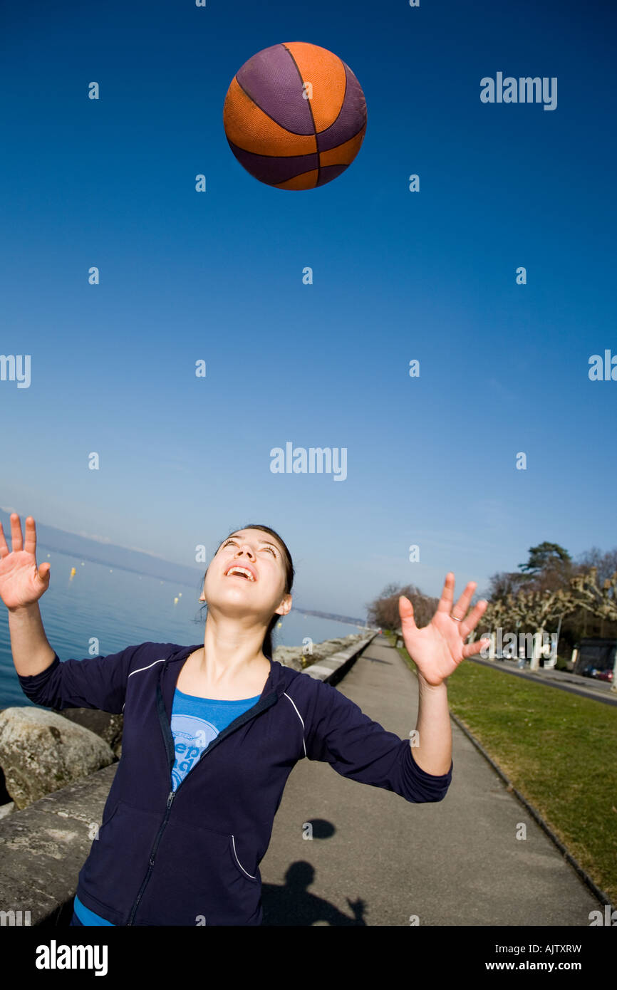 Woman juggle with a basket ball on a shoreline - Stock Image