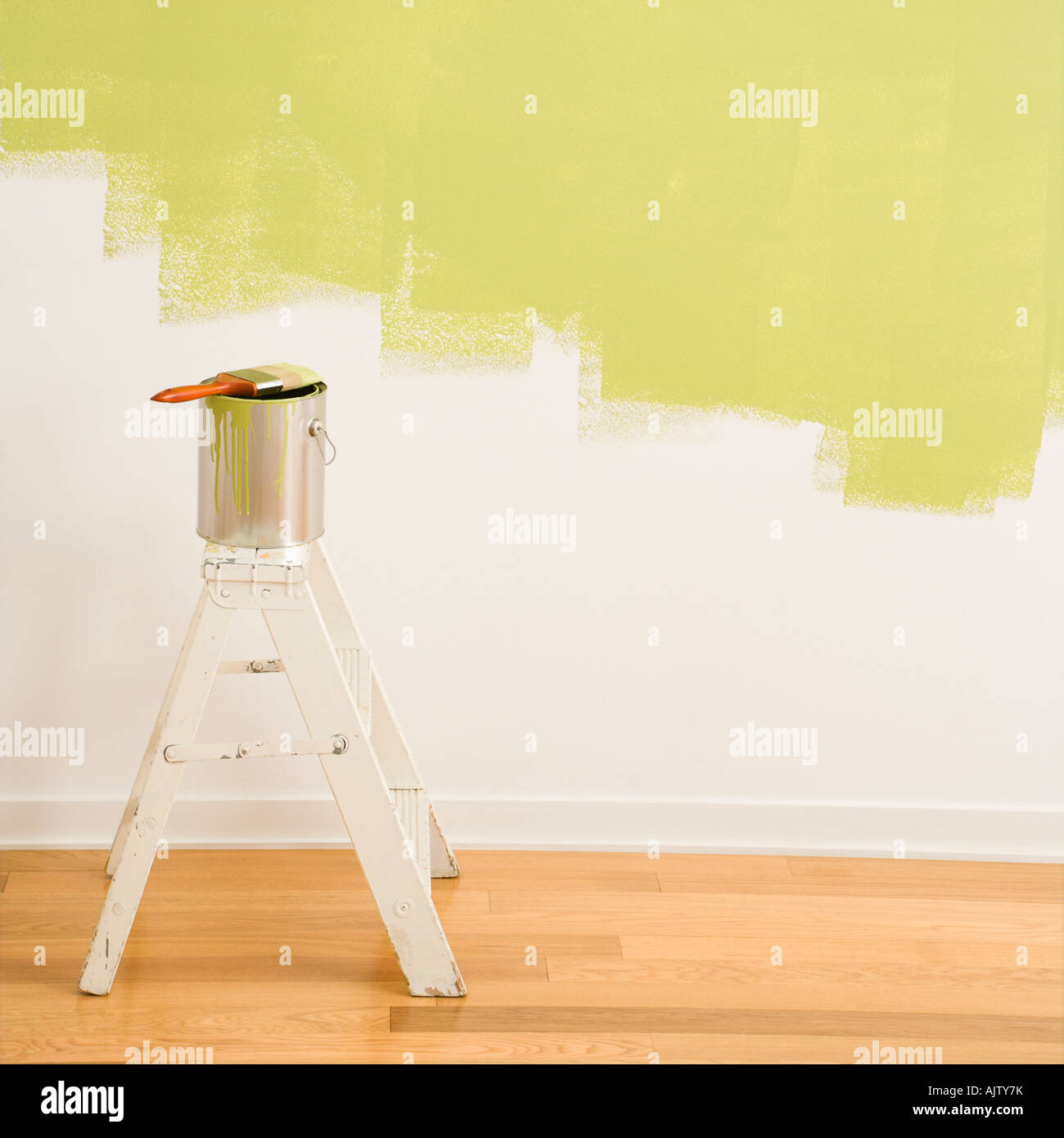 Paintbrush on can on top of step ladder with painted wall Stock ...