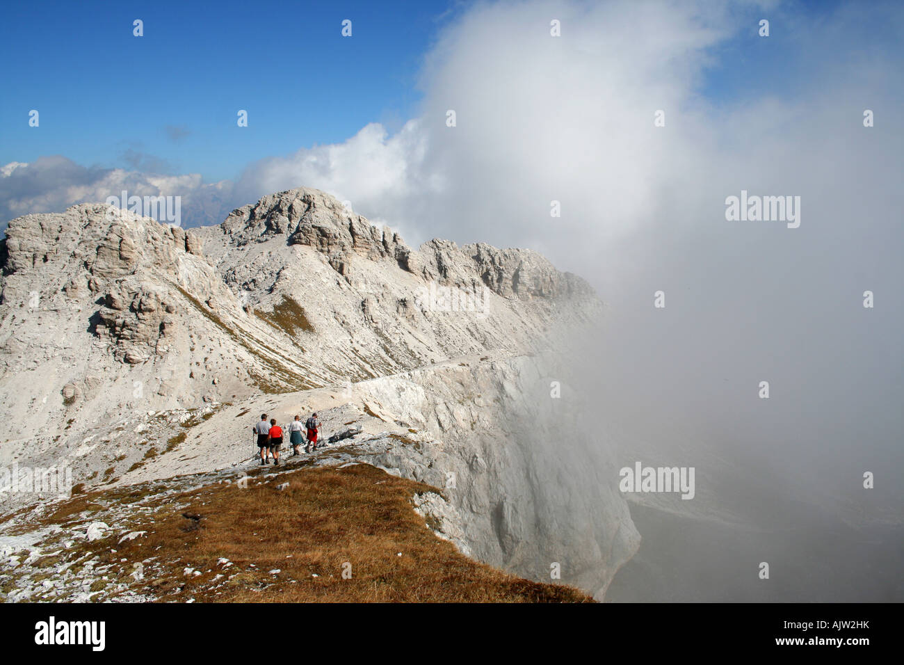Walkers on the Alta Via 1 in mist on Cima di Zita, Dolomiti Bellunesi, Veneto, Italy - Stock Image