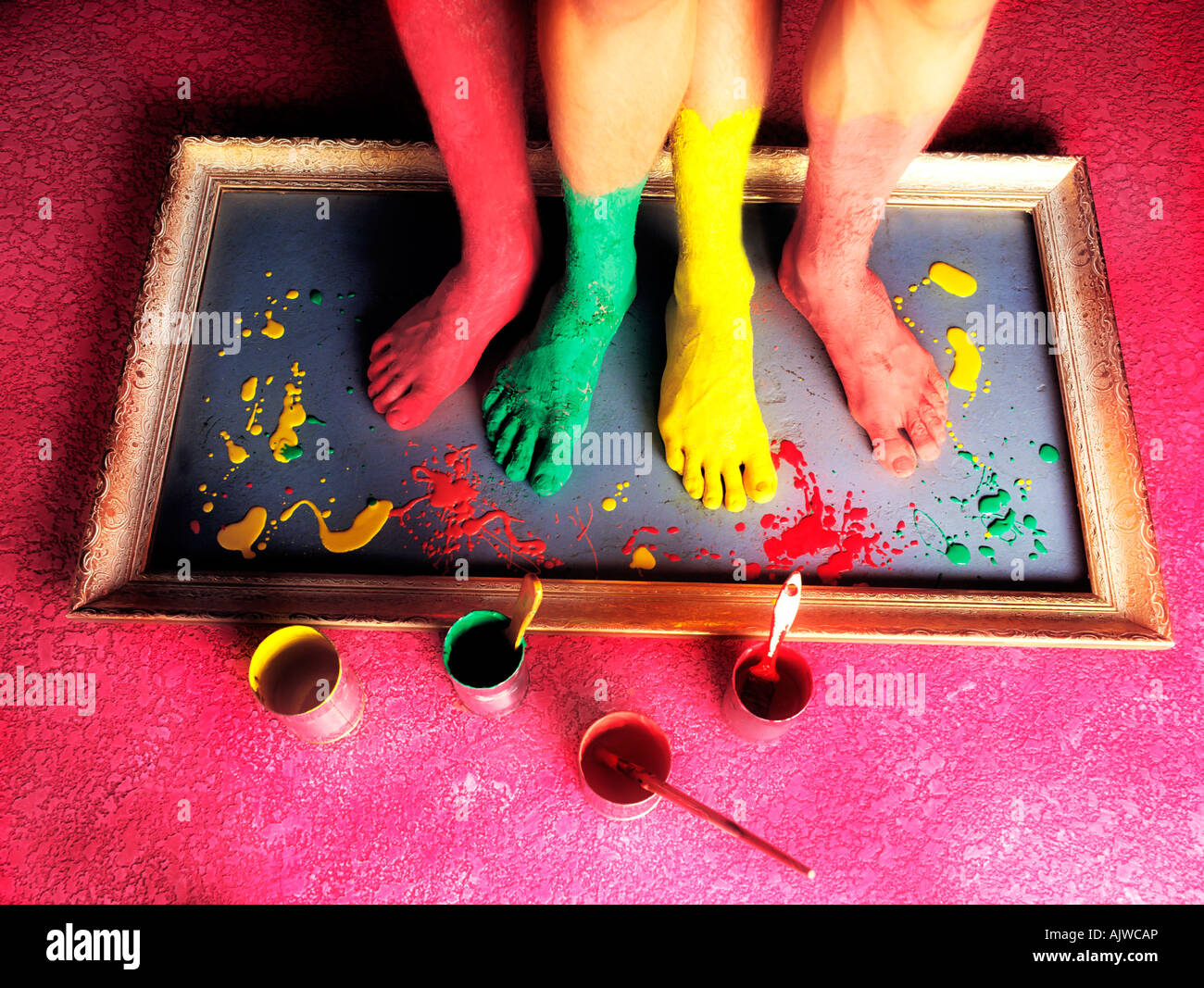 Painted bare feet standing on a picture frame - Stock Image