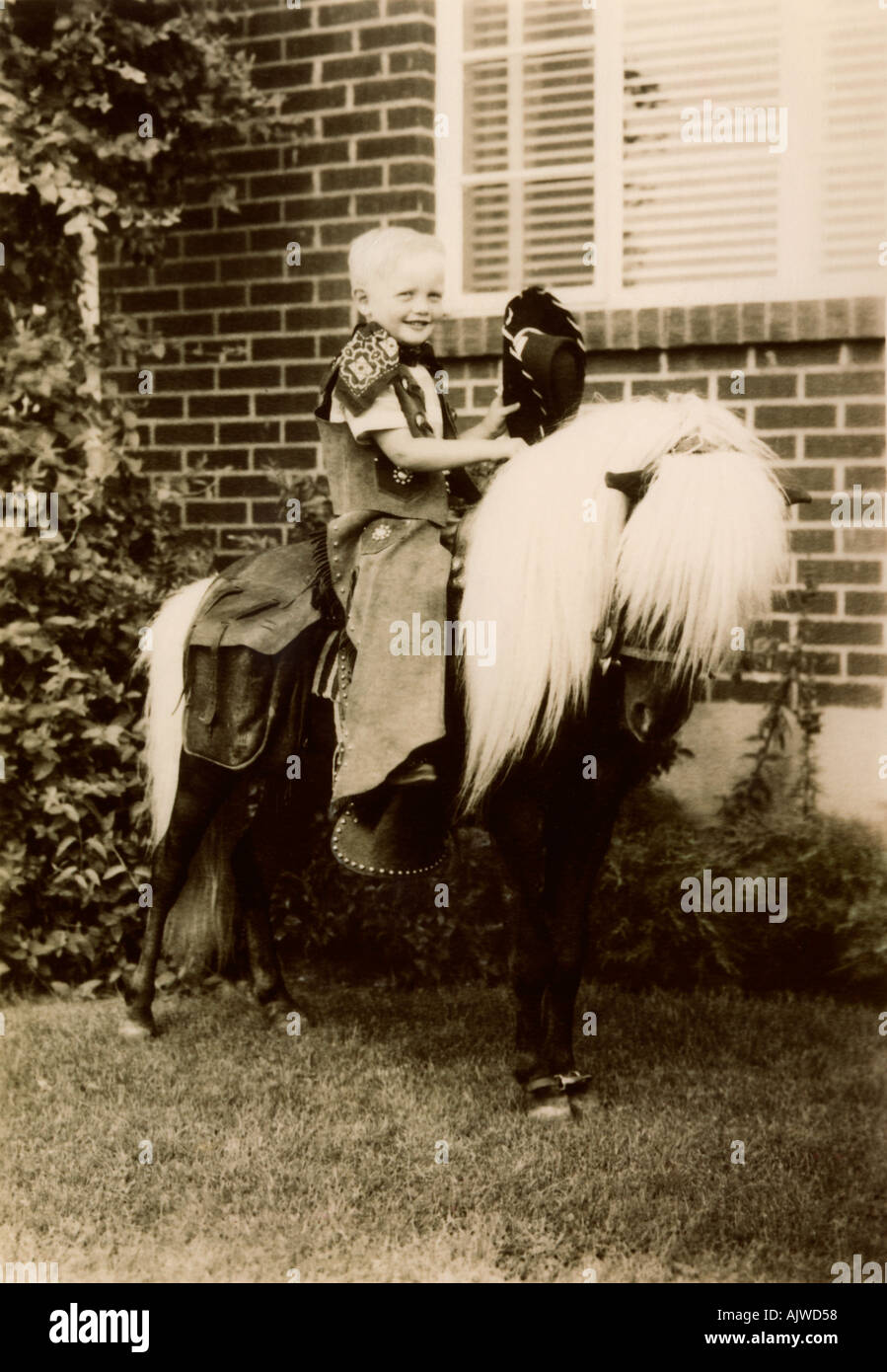 1950 s portrait of a young boy dressed in a cowboy suit sitting on a shetland pony - Stock Image