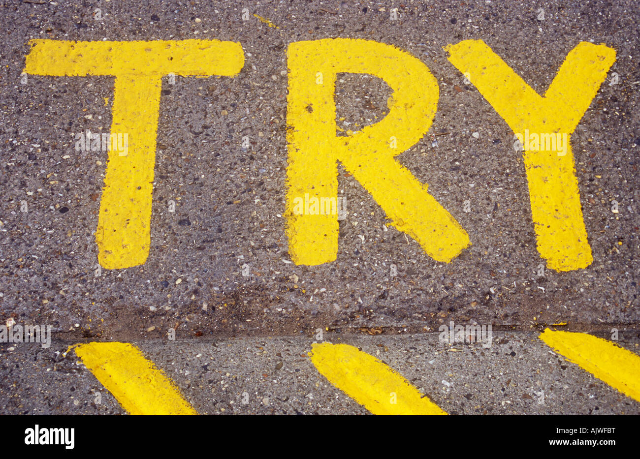 Yellow letters stating TRY and diagonal yellow hatched lines unevenly painted on concrete - Stock Image