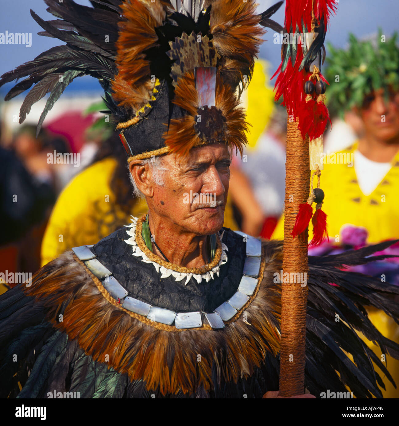 Portrait of traditional French Polynesian tribal chief holding rope bound stave with red feathers at the Pacific Arts Festival - Stock Image