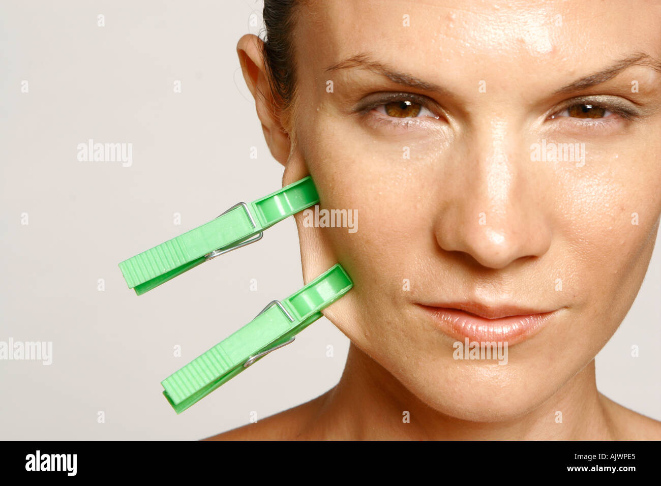 beauty head shot of a woman with two green pegs - Stock Image