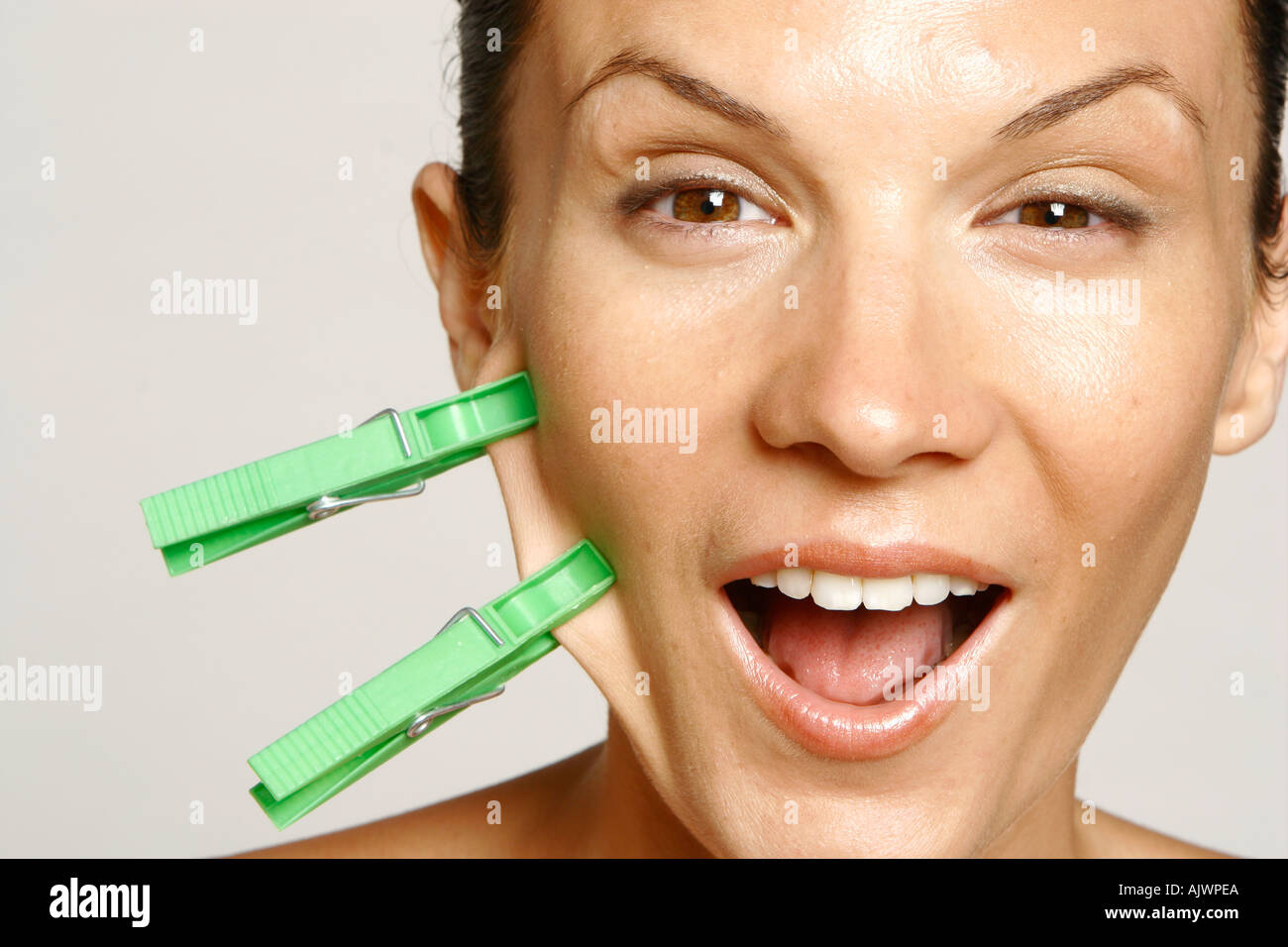 beauty head shot of a woman with two green pegs attached to her cheek - Stock Image