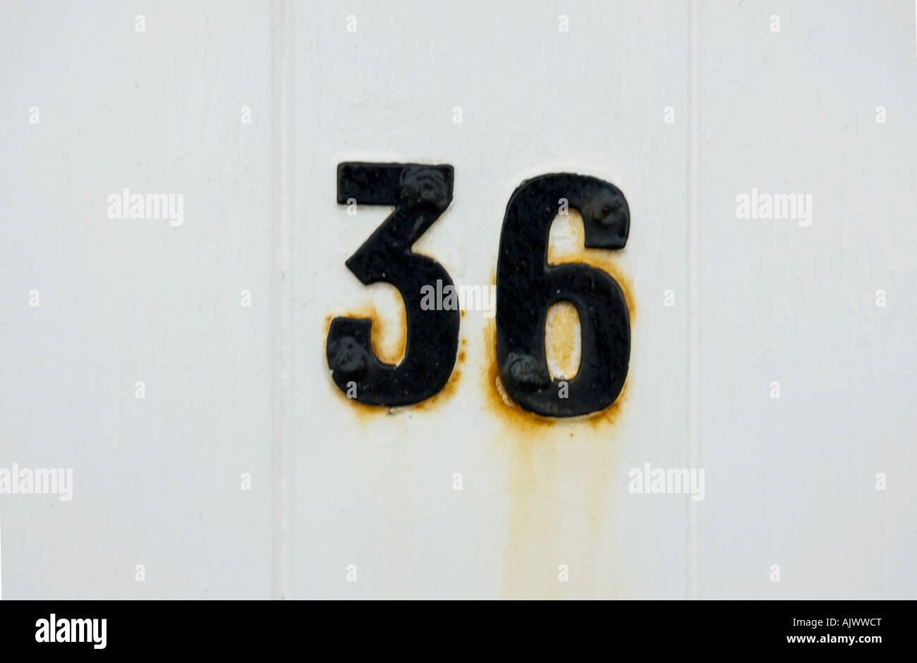 Number 35 in metal letters on a white wooden door - Stock Image