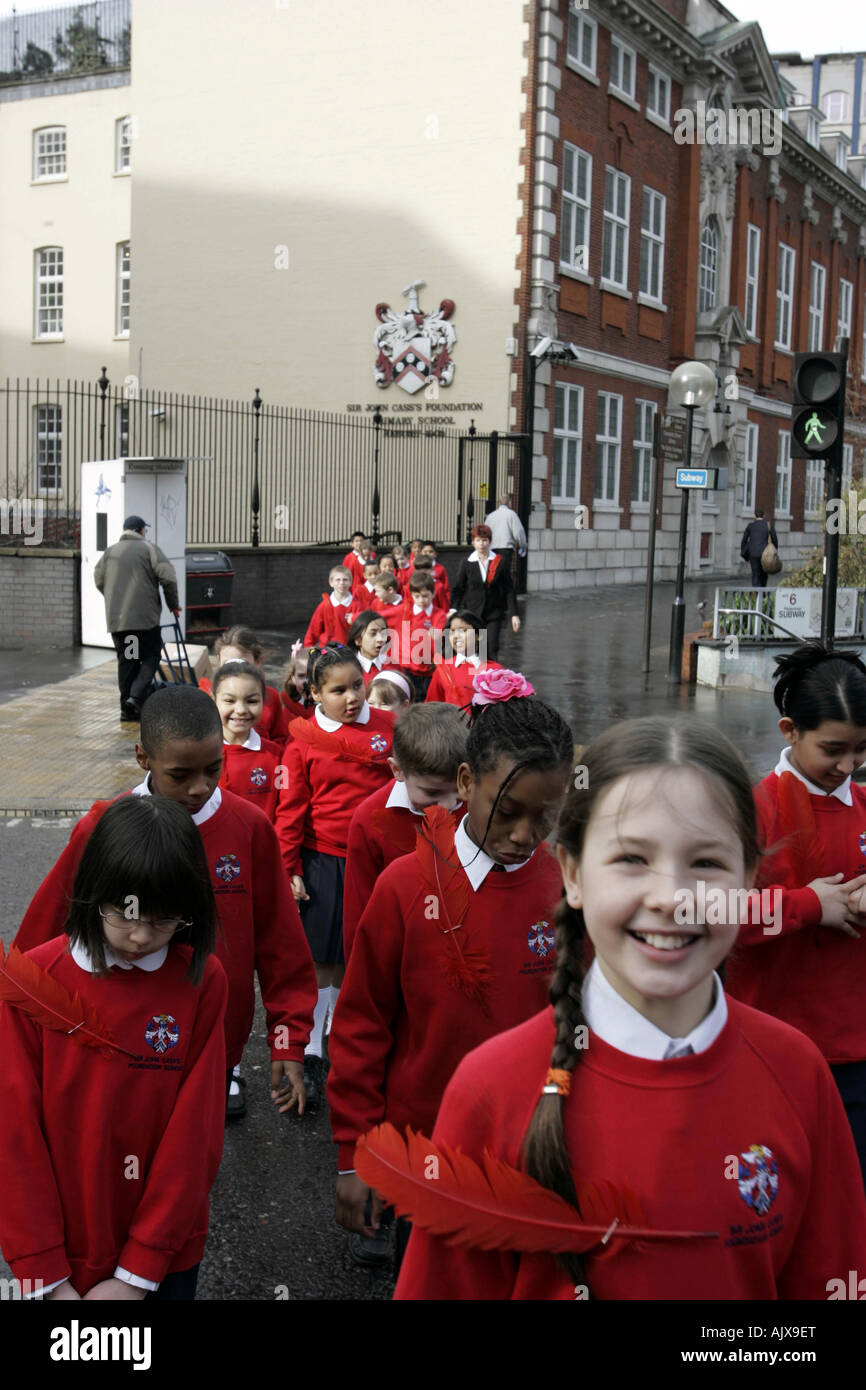 Schoolchildren crossing the road at traffic-light London England UK - Stock Image