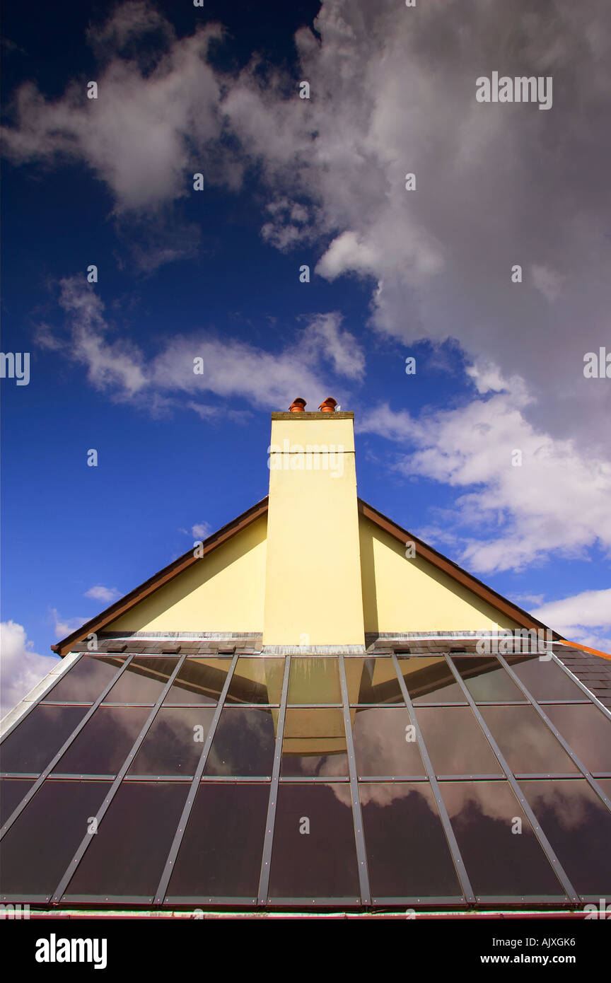 Solar panels on a rooftop in Devon, UK, reflecting a pitched roof and chimney against a blue sky with clouds. - Stock Image